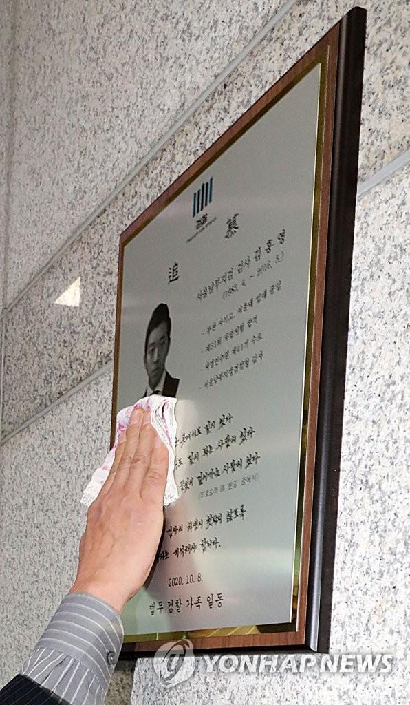 지난해 10월 8일 오전 양천구 서울남부지검에서 고(故) 김홍영 검사의 아버지가 김 검사의 추모패를 손수건으로 닦고 있다.