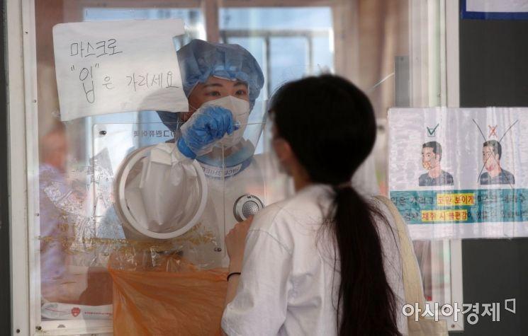 20일 서울역 광장에 마련된 임시 선별검사소에서 의료진이 시민의 검체를 채취하고 있다./김현민 기자 kimhyun81@