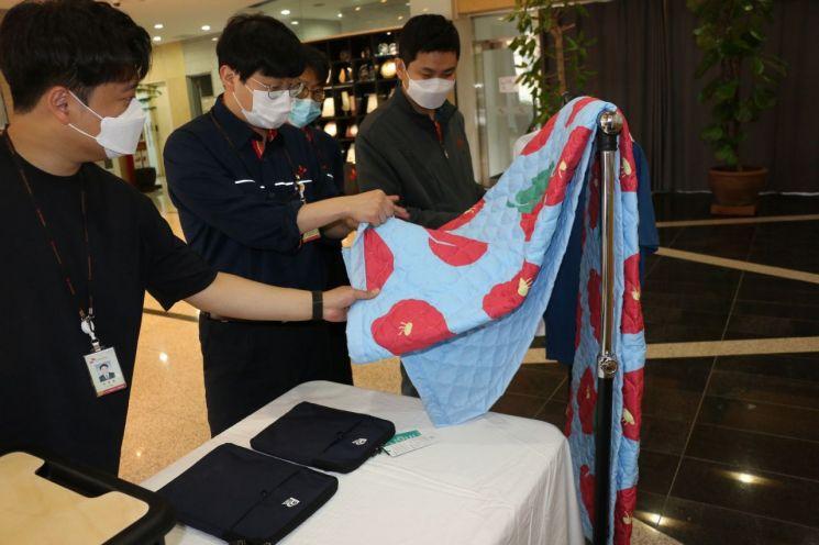 SK인천석유화학 직원이 폐플라스틱을 재활용해 만든 담요를 살펴보고 있다. 사진제공=SK이노베이션