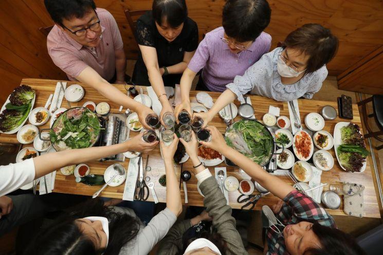 광주에서 사적 모임이 8명까지 가능해진 지난 18일 오후 광주 북구청 인근 식당에서 북구청 공무원들이 지역 상권 활성화를 위해 구내식당에서 벗어나 오랜만에 8명이 모여 식사를 하며 음료수로 건배를 하고 있다. [이미지출처=연합뉴스]
