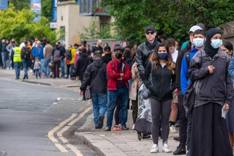 영국에서 코로나19 델타 변이 바이러스가 급속히 확산하는 가운데 지난 19일(현지시간) 런던 북서부 브렌트의 한 백신접종센터 앞에 시민들이 줄지어 서 있다. [이미지출처=신화연합뉴스]