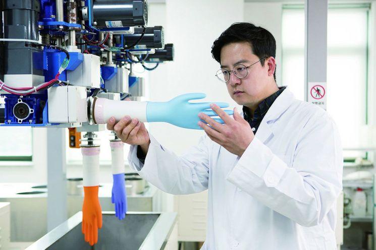 금호석유화학 연구원이 라텍스 제품으로 만든 장갑을 살펴보고 있다.<사진제공:금호석유화학>