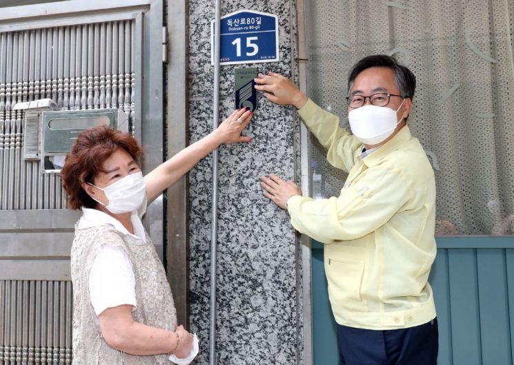 유성훈 금천구청장(사진 오른쪽)이 23일 월남참전 국가유공자 채희택 씨 댁을 찾아 국가유공자 명패를 달아드리고 있다.