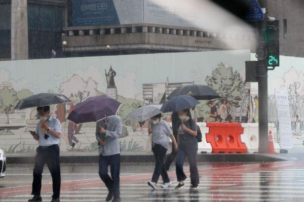 23일 오후 서울 광화문광장에서 우산을 쓴 시민들이 발걸음을 재촉하고 있다. [이미지출처=연합뉴스]
