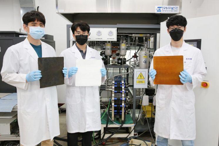 한국에너지기술연구원 연구진이 개발한 10kW 알칼라인 수전해 스택 앞에서 스택에 사용 된 전극과 분리막을 들고 있다. 사진제공=한국에너지기술연구원.