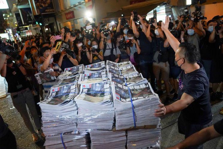 24일 홍콩에서 반중매체 빈과일보가 폐간하기 전 마지막으로 내놓은 신문을 사기 위해 사람들이 모여들고 있다. [이미지출처=로이터연합뉴스]