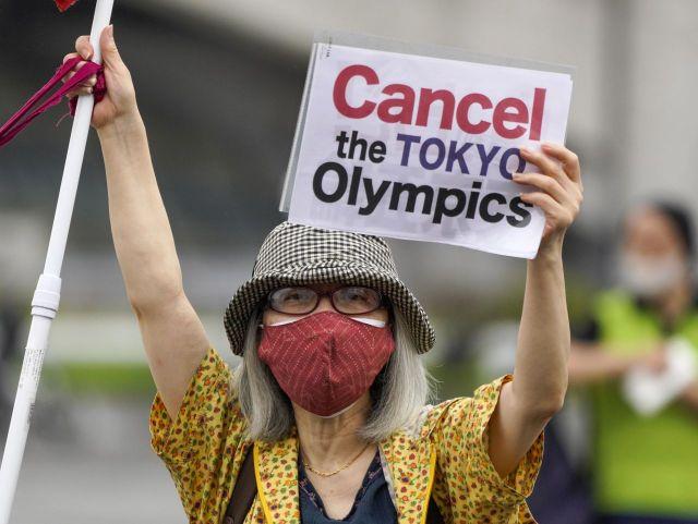 9일 도쿄올림픽 성화 도착 행사가 열린 일본 도쿄의 고마자와 올림픽공원 체육관 앞에서 한 여성이 피켓을 든 채 올림픽 개최 반대 시위를 벌이고 있다. /도쿄 EPA=연합뉴스