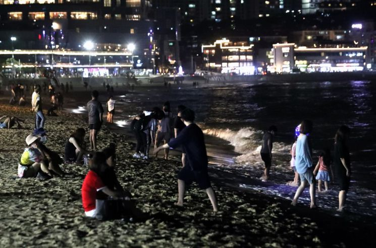 야간 해운대해수욕장에서 더위를 식히고 있는 피서객들. [이미지출처=연합뉴스]
