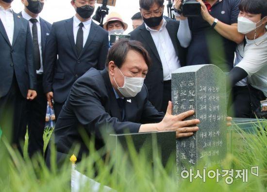 야권 대선주자인 윤석열 전 검찰총장이 광주 운정동 민족민주열사묘역(옛 망월묘역)에서 이한열 열사 묘비를 어루만지고 있다.
