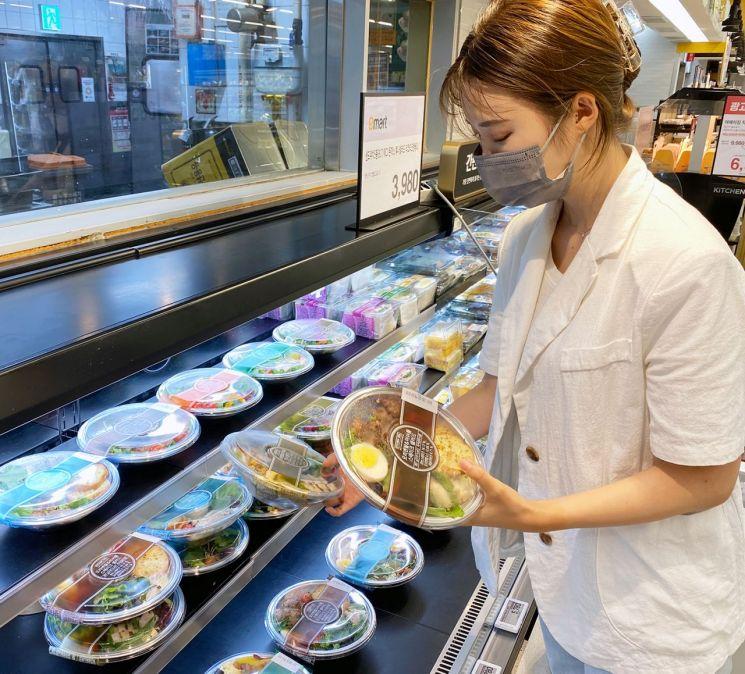 고객이 마트에서 샐러드를 구입하고 있다.