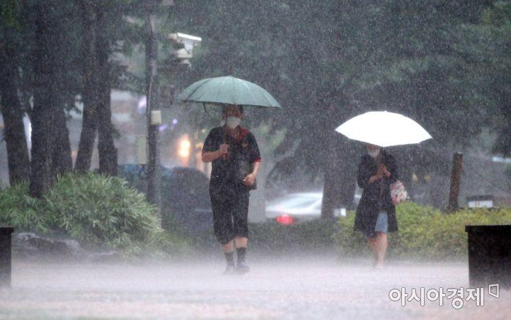 서울 지역에 국지성 호우가 내린 19일 서울 광화문 인근 거리에서 시민들이 우산을 쓴 채 발걸음을 재촉하고 있다./김현민 기자 kimhyun81@