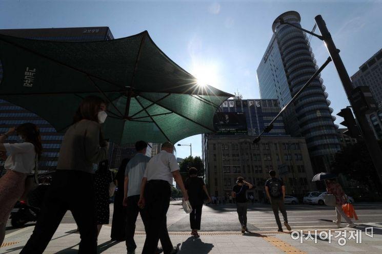 절기상 중복(中伏)이자 찜통더위가 절정에 달한 21일 서울 종로구 광화문 사거리에서 출근길 시민들이 발걸음을 재촉하고 있다. /문호남 기자 munonam@