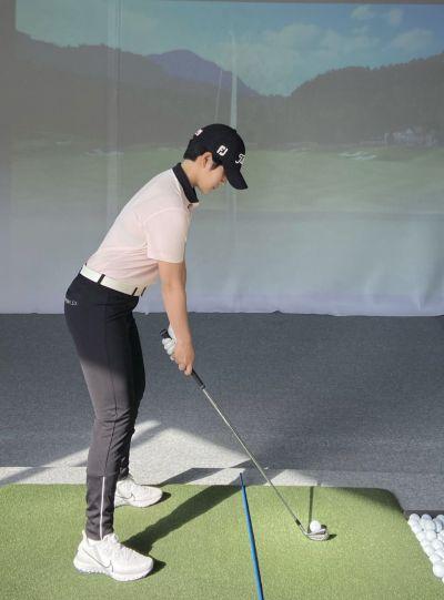 <사진1> 공과 몸 사이에 여분의 골프채를 놓고 클럽과 스탠스가 일치하는지 살핀다.
