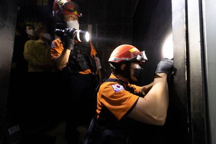 이재명 경기도지사와 함께 심야영업 업소 합동단속에 나선 소방 공무원들이 해당 업소의 문을 강제로 열고 있다.