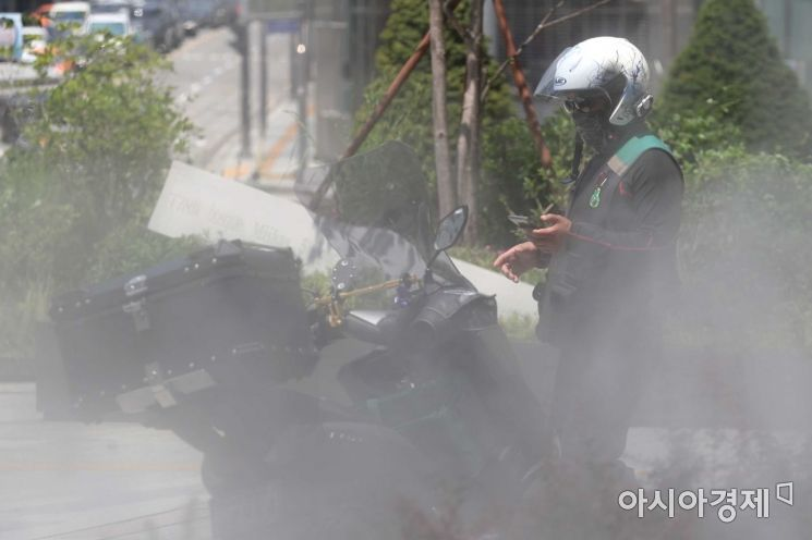 가마솥 더위가 이어진 23일 서울 중구 명동 중앙우체국 앞 물안개 분수에서 배달원이 분주하게 이동하고 있다. /문호남 기자 munonam@