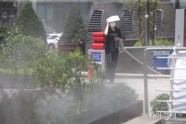 가마솥 더위가 이어진 23일 서울 중구 명동 중앙우체국 앞 물안개 분수에서 한 시민이 종이로 햇볕을 막으며 이동하고 있다. /문호남 기자 munonam@