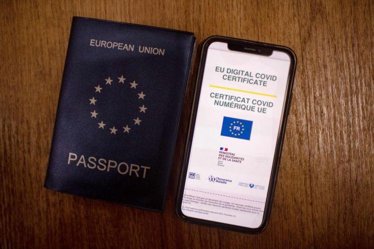휴대전화에 비치는 'EU 디지털 코로나19 증명서'       (파리 AFP=연합뉴스) 유럽연합(EU) 역내 자유로운 이동을 위한 EU 디지털 신종 코로나바이러스 감염증(코로나19) 증명서 제도가 1일(현지시간) 정식 시행에 들어갔다. 이 증명서는 코로나19 접종자는 물론 코로나19에 걸렸다가 회복했거나 음성 판정을 받은 EU 시민과 거주자에게 발급된다. 디지털이나 QR코드가 포함된 종이 형태로 사용이 가능하다. 사진은 휴대전화 화면에 나타난 EU 디지털 코로나19 증명서(오른쪽)와 여권.     leekm@yna.co.kr (끝)   <저작권자(c) 연합뉴스, 무단 전재-재배포 금지>