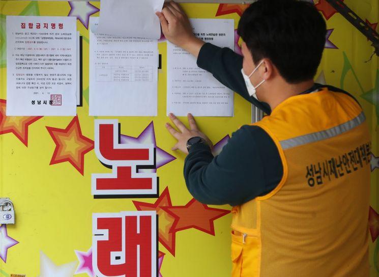 경기도 성남시의 한 노래방에서 성남시 공무원이 집합금지 행정명령서를 붙이고 있다. 사진 = 연합뉴스