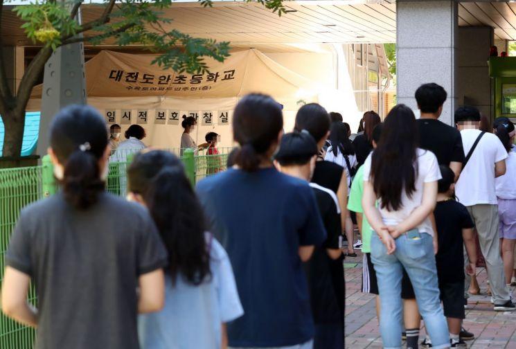 지난 22일 대전시 서구 도안동에 마련된 임시 선별검사소에서 초등학생과 어린이들이 검사받기 위해 대기하고 있다. [이미지출처=연합뉴스]