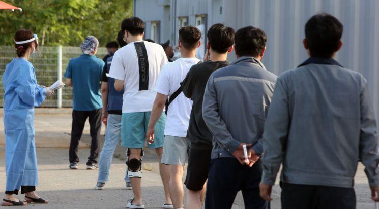 지난 21일 강원도 강릉 임시선별검사소에서 직장인들이 퇴근하면서 코로나19 검사를 받기 위해 줄지어 서 있다. [이미지출처=연합뉴스]