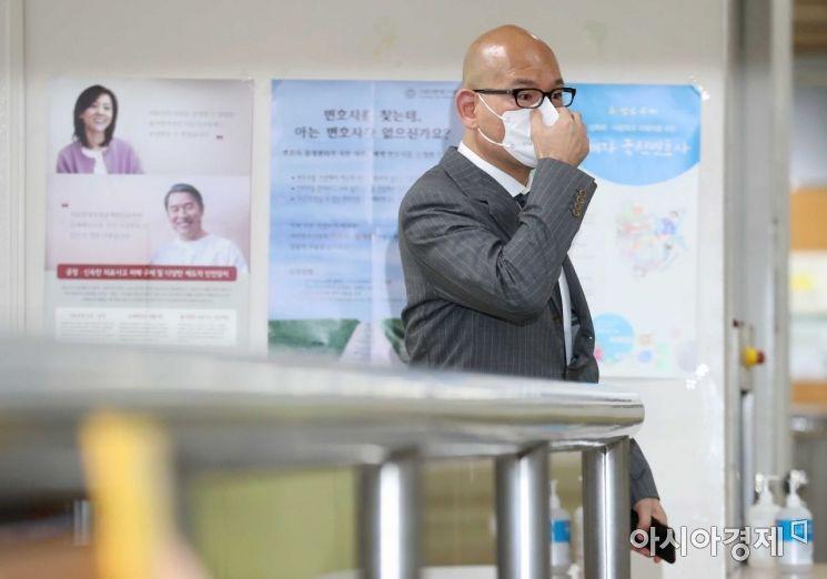 이해욱 DL그룹 회장이 취재진을 본 뒤 마스크를 매만지고 있다. /문호남 기자 munonam@