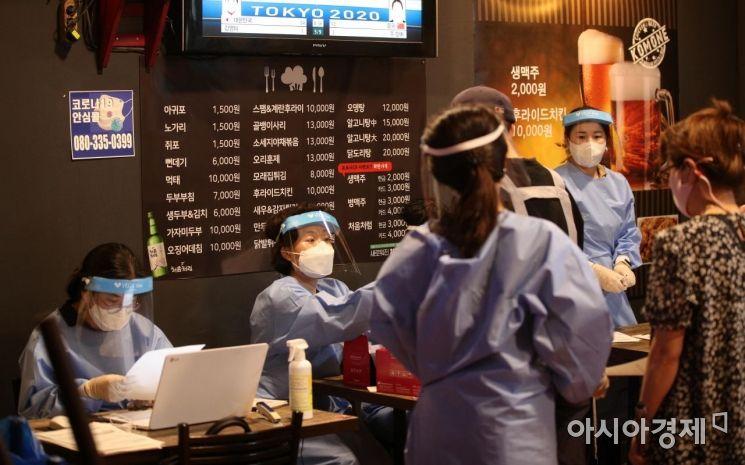 27일 서울 중구 인현시장의 한 호프집에 마련된 '찾아가는 선별검사 기동대'에서 인근 상인들이 코로나19 선제 검사를 받고 있다. /김현민 기자 kimhyun81@
