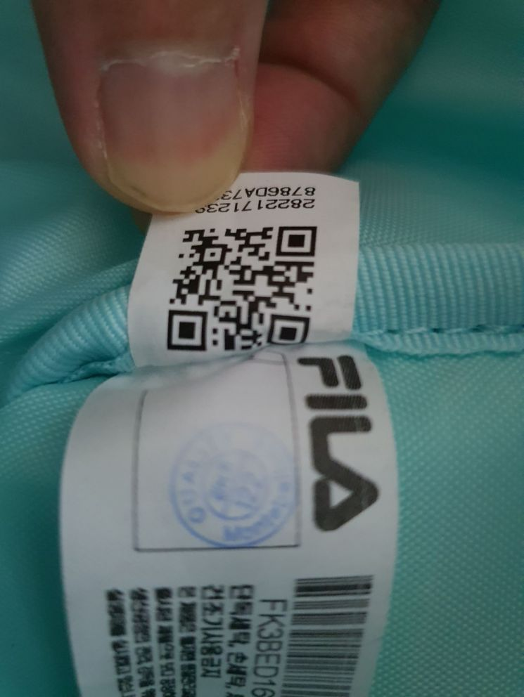 휠라 제품 태그에 QR코드가 삽입 돼 있다.