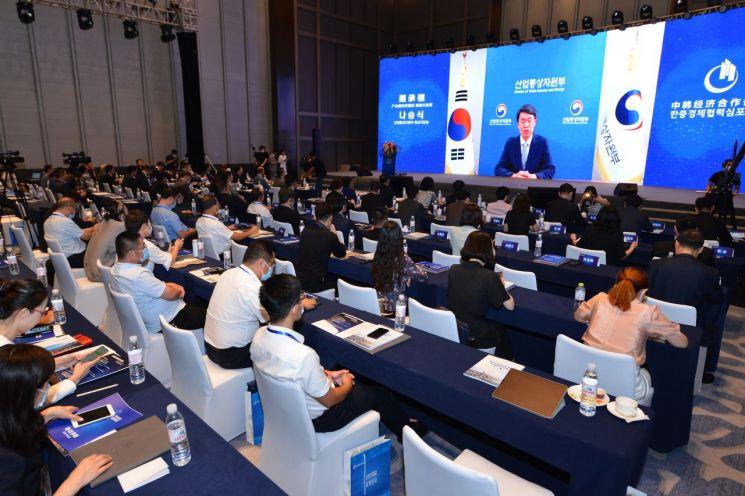 KOTRA는 주칭다오 총영사관과 함께 28일 중국 산둥성 칭다오에서 '한·중 경제협력 심포지엄'을 개최했다. 이날 오전에 열린 포럼에 참가한 한·중 기업인들이 나승식 산업통상자원부 통상차관보의 축사 영상을 보고 있다./사진제공=KOTRA