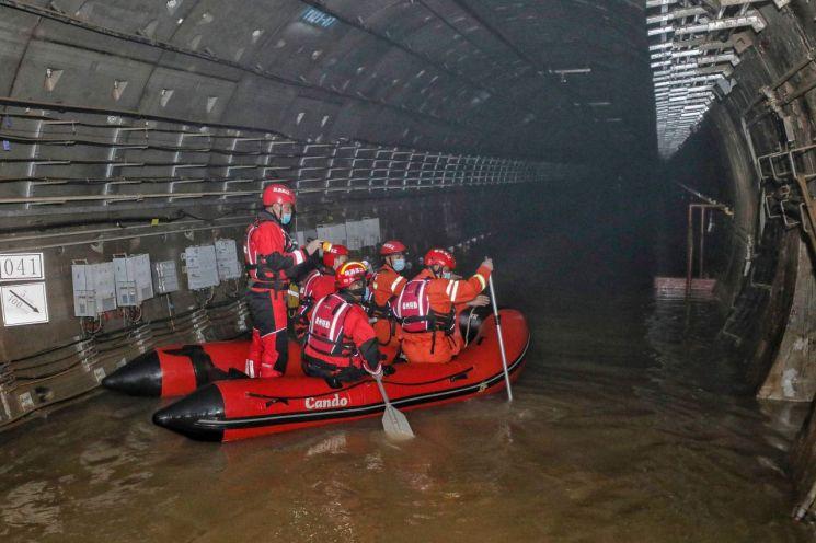 중국 중부 허난(河南)성에 최근 내린 기록적 폭우로 침수된 정저우의 지하철 터널에서 지난 26일 구조대원들이 보트를 저으며 수색 작업을 하고 있다. [이미지출처=AFP연합뉴스]