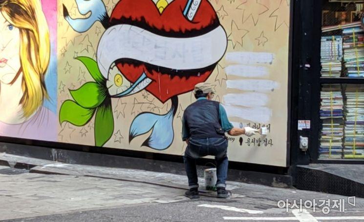 30일 오전 9시30분께 서점 관계자가 나와 '쥴리 벽화'에서 문구를 지우고 있다. 사진=윤슬기 인턴기자 seul97@asiae.co.kr