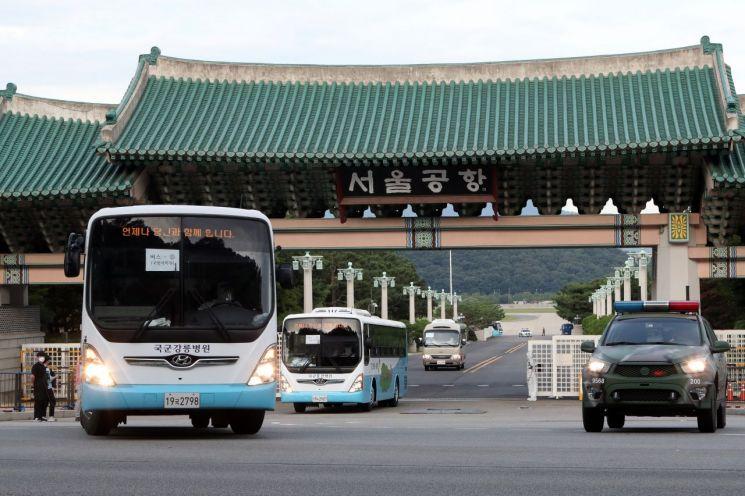지난 20일 오후 청해부대 34진 장병을 격리·치료 시설로 이송 중인 버스가 서울공항 정문을 나서고 있다. [이미지출처=연합뉴스]