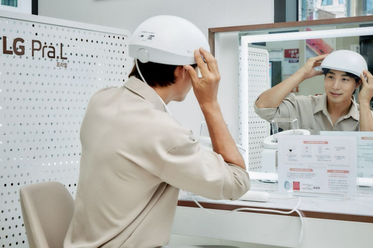 LG전자 모델이 서울 관악구 LG베스트샵 봉천점에 설치돼 있는 LG 프라엘 메디헤어 전용 체험공간에서 메디헤어를 착용해보고 있다.(사진제공=LG전자)