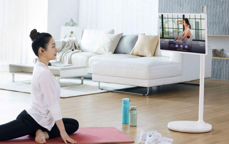모델이 LG 피트니스 애플리케이션(앱)으로 피트니스 영상을 보며 스트레칭을 하고 있다.(사진제공=LG전자)