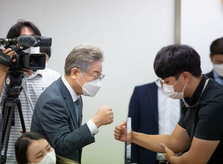 이재명 경기도지사가 부산지역 청년간담회에 참석한 청년과 주먹 인사를 하고 있다.
