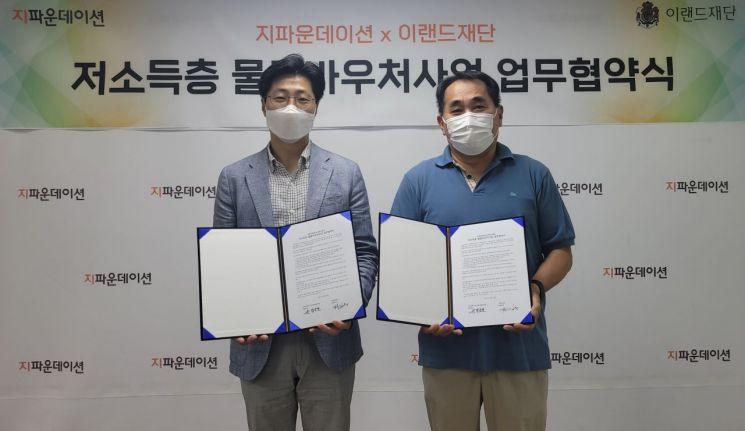 김욱 이랜드국장국장(왼쪽)과 정순호 지파운데이션 실장이 저소득층 물품바우처사업을 위한 업무협약을 체결한 뒤 기념촬영을 하고 있다.
