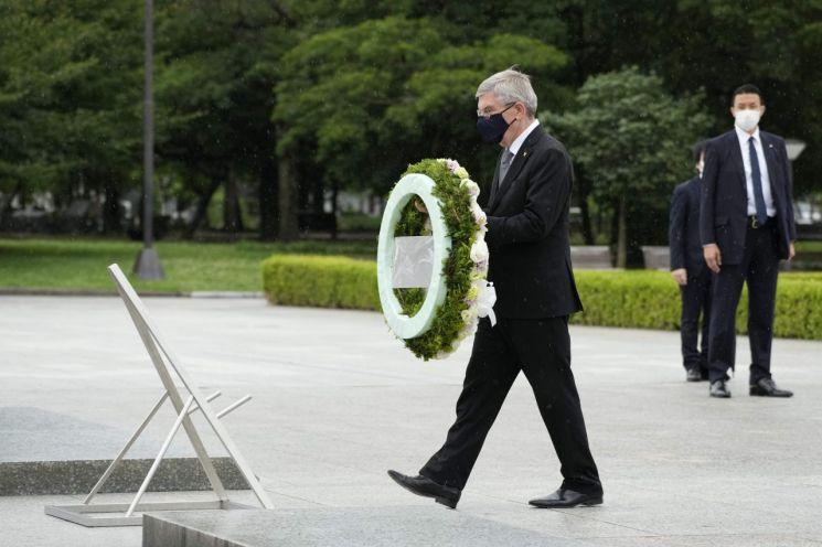 지난달16일 일본 히로시마 평화기념공원을 방문한 토마스 바흐 국제올림픽위원회(IOC) 위원장이 태평양전쟁 원폭 희생자 위령비 앞에 헌화하고 있다. [이미지출처=연합뉴스]