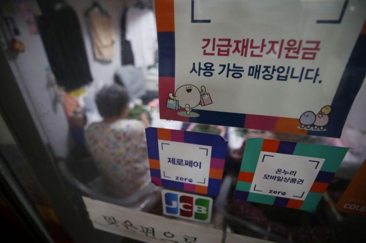2일 오후 서울 종로구 통인시장 한 가게에 붙은 긴급재난지원금 사용 가능 안내 문구. [이미지출처=연합뉴스]
