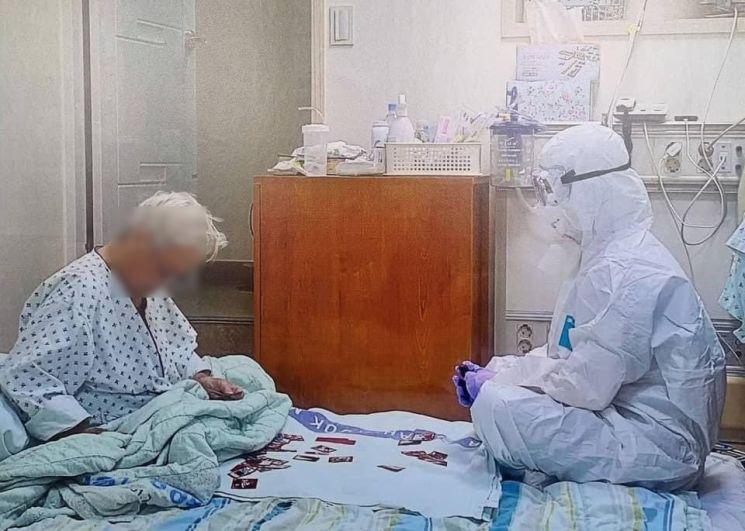 1일 방호복을 입은 의료진과 할머니가 앉아 화투 치는 모습이 공개돼 화제가 됐다./사진=트위터 캡처