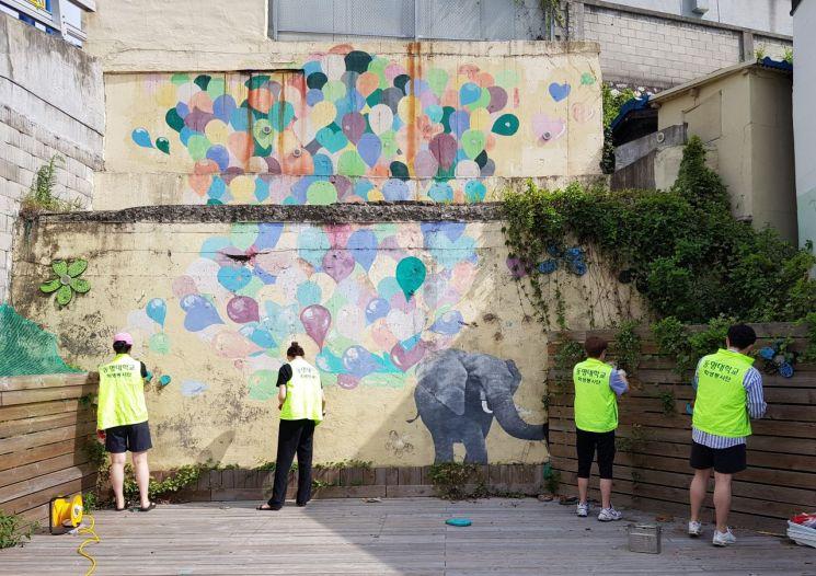동명대 학생들이 우암동 '달동네'에서 벽화를 완성해가고 있다.
