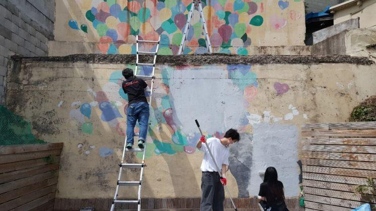 벽화 화가로 나서 구슬땀을 흘리고 있는 동명대 학생들.
