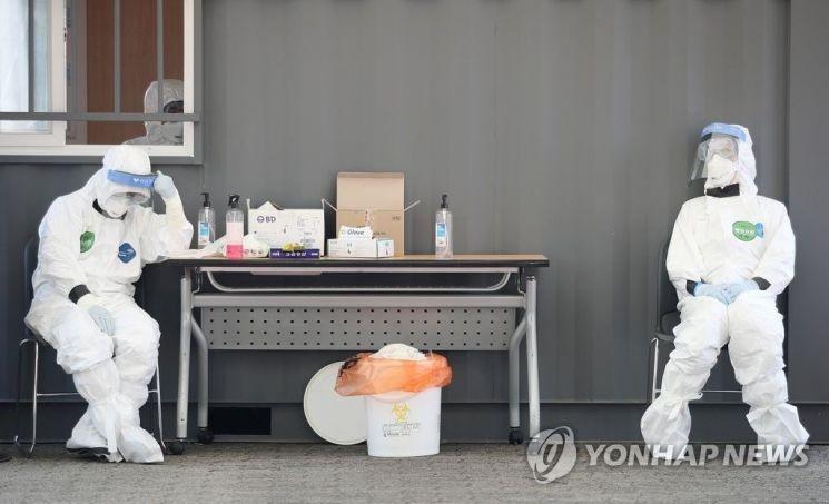 지난해 3월23일 오후 송파구 잠실야구장에 설치된 드라이브 스루 선별진료소에서 의료진이 의자에 앉아 잠시 쉬고 있다. / 사진=연합뉴스