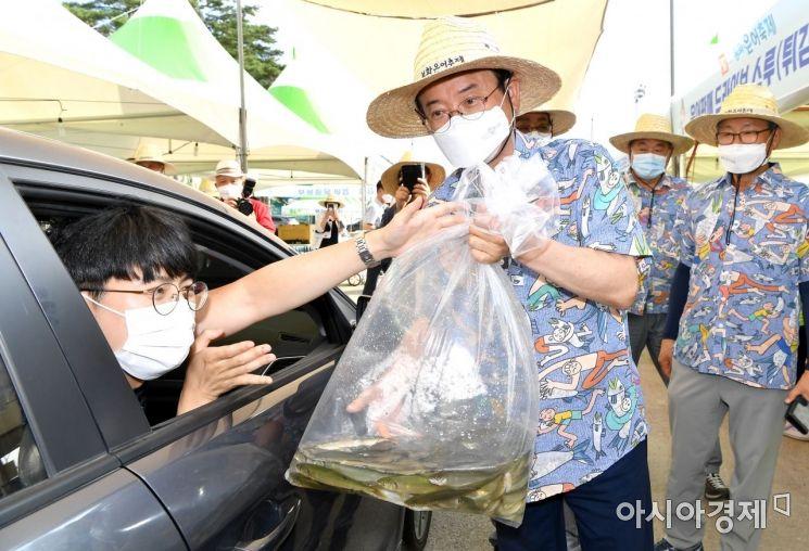 이철우 지사가 4일 봉화군 은어 축제장의 드라이브 스루 판매장에서 방문객에게 직접 상품을 전달하고 있다.