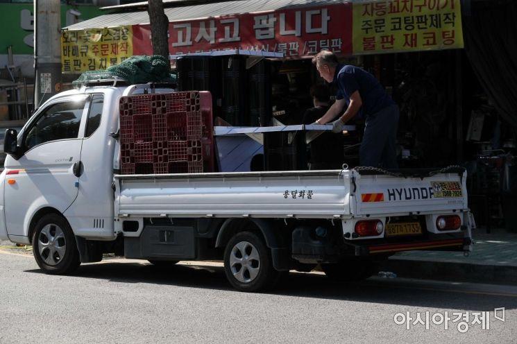 한 상인이 중고 집기를 옮기고 있다. 길에 손님은 없고 중고품을 실은 트럭만 지나다닌다. /문호남 기자 munonam@