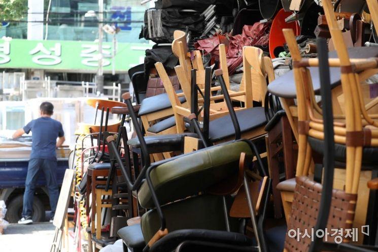 코로나19 장기화로 소상공인과 자영업자의 주름이 깊어지고 있는 5일 서울 황학동 주방거리에서 한 상인이 중고 집기를 옮기고 있다. 사람 키만 한 중고품이 골목을 가득 메우고 있다. /문호남 기자 munonam@