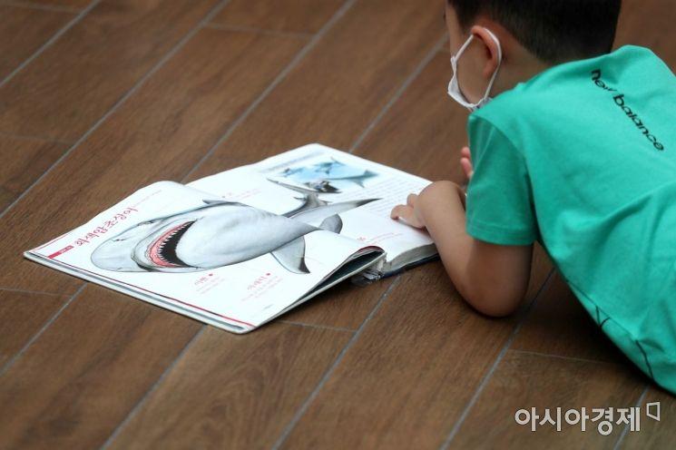 '나는 상어 박사' 한 어린이가 바닥에 앉아 책을 보고 있다. /문호남 기자 munonam@