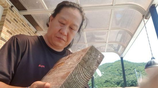 진성영 작가가 명패 작업을 위해 바닷가에서 수거해 온 빈티지 폐목을 살펴보고 있다.