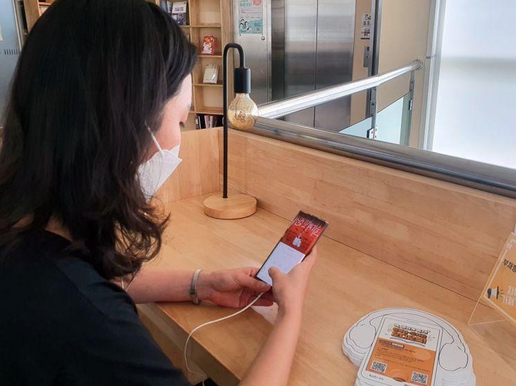 모바일 기기를 이용하여 성북구립도서관 오디오북 서비스를 이용하고 있는 시민