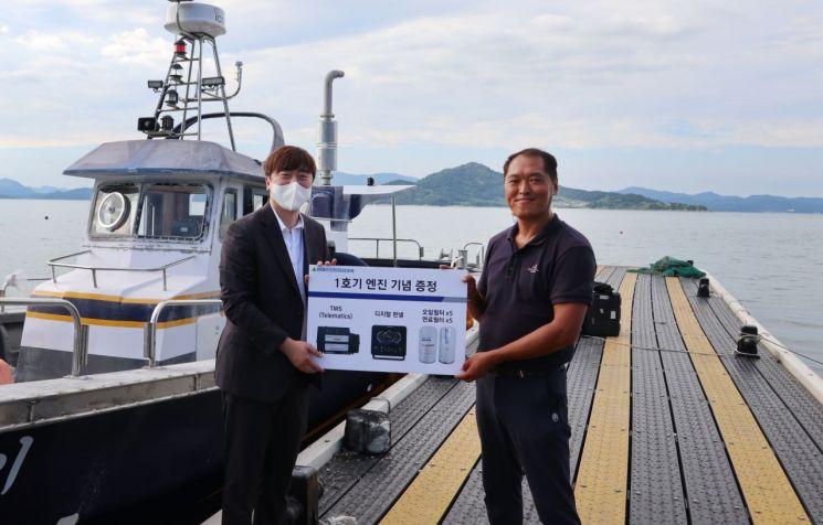 현대두산인프라코어 관계자가 전자식 선박엔진 DX12 모델 1호기 엔진 탑재 고객에게 기념품을 증정하고 있다.