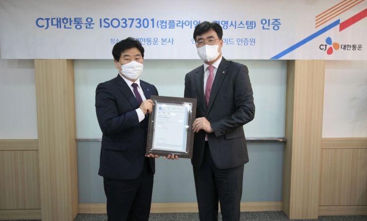 CJ대한통운 본사에서 열린 ISO37301 인증 수여식에서 장윤석 CJ대한통운 법무·Compliance 실장(오른쪽)과 이일형 로이드인증원 한국지사 대표(왼쪽)가 기념촬영을 하고 있다.