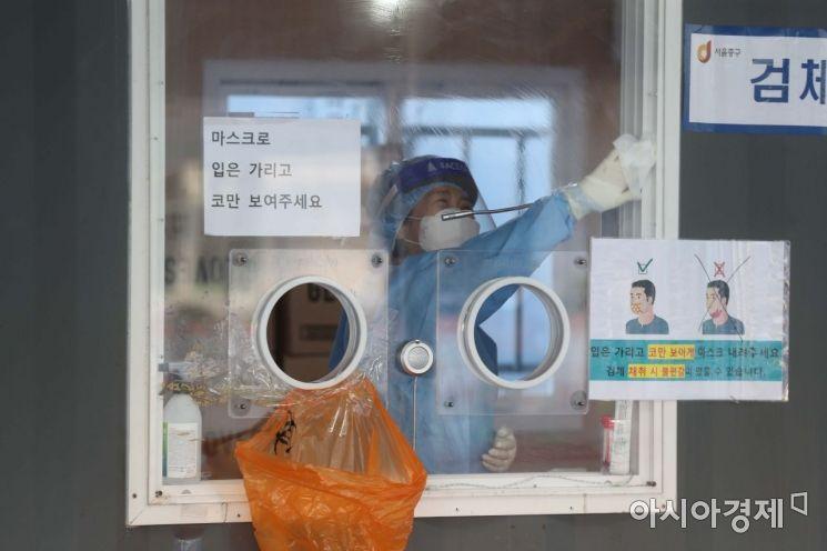 수도권을 중심으로 코로나19 확산세가 거세지고 있는 15일 서울역 광장에 마련된 임시 선별검사소에서 의료진이 유리벽을 소독하고 있다. /문호남 기자 munonam@